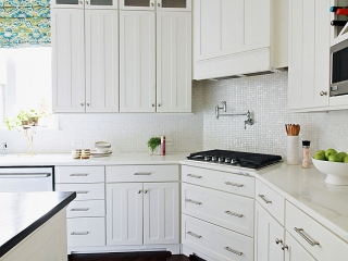 kitchen design with mother of pearl tile, white cabinets, custom cabinets and range hood, potfiller and hardwood floors on the main line philadelhpia
