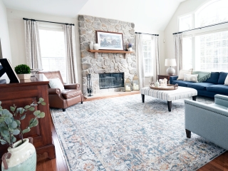 family room design in Phoenixville PA with stone fireplace, wood floating mantle, hardwood floors, navy sofa, fabric ottoman