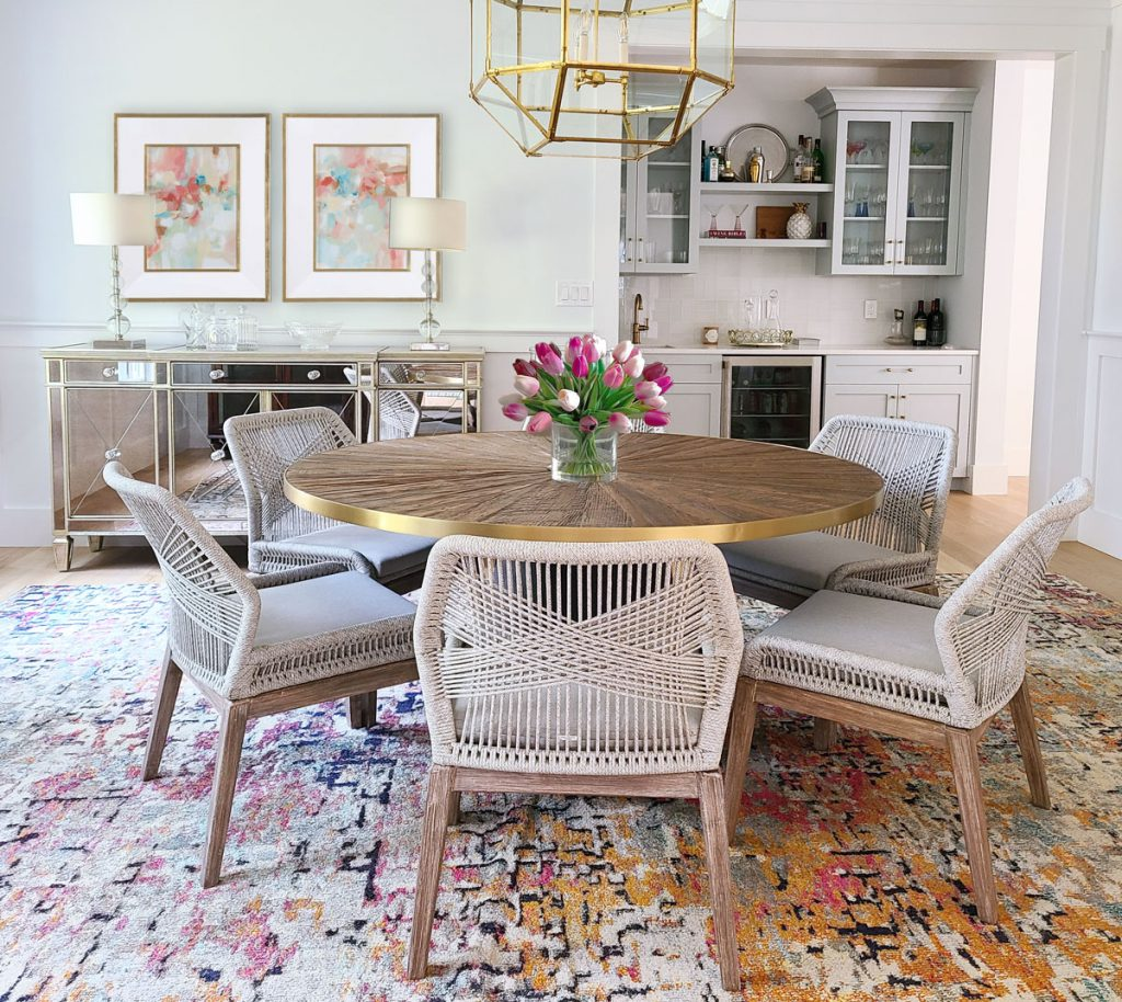 colorful dining room design on Main Line PA featuring round pedestal dining table with gold accents