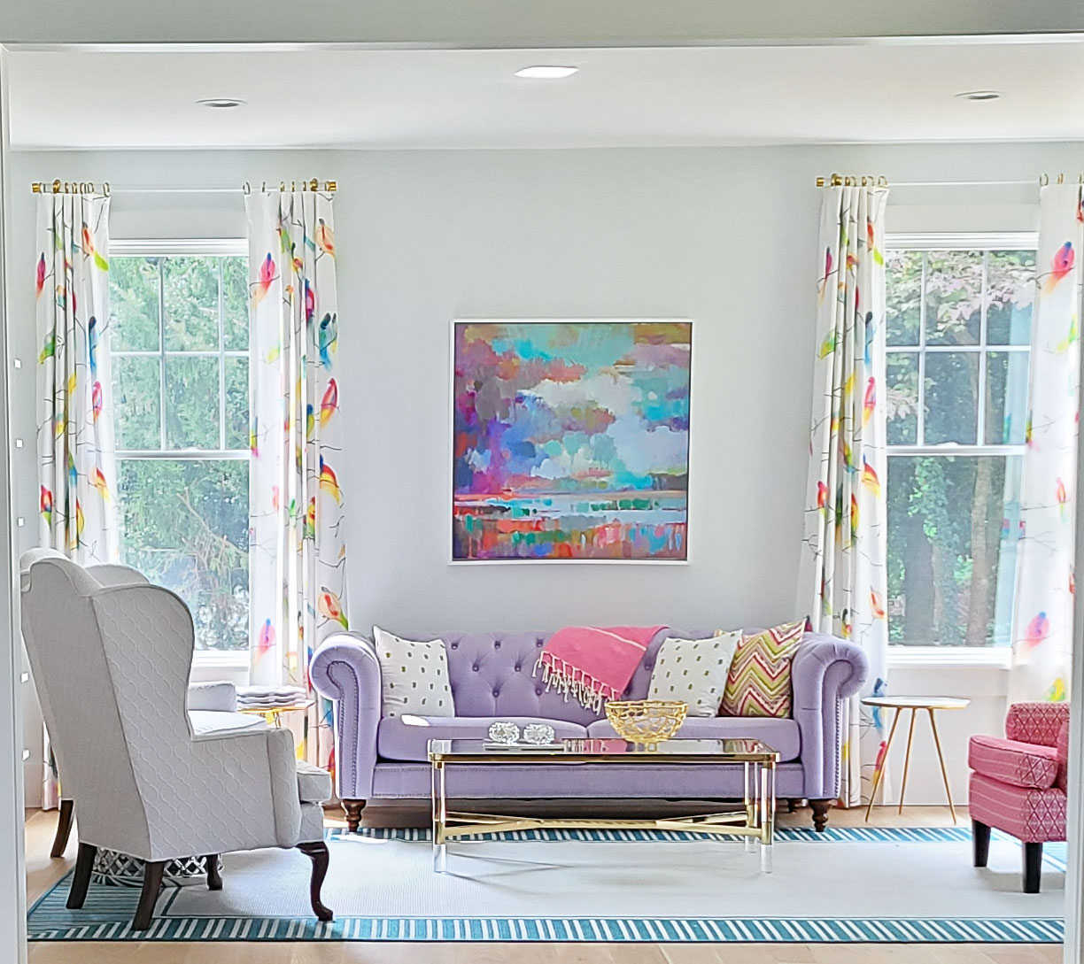 colorful living room design in Devon PA home. Off white walls, lavander couch, bird print window treatments